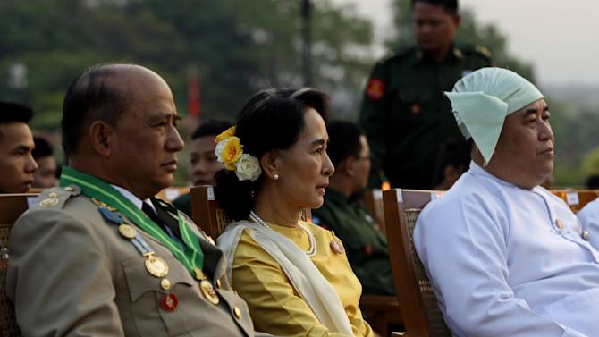Opposition leader Aung San Suu Kyi, in yellow, and Deputy Border Affairs Minister Maj. Gen. Zaw Win, left, attend Myanmar's 68th anniversary celebrations of Armed Forces Day, in Naypyidaw, Myanmar, Wednesday, March 27, 2013. The daughter of Aung San, Myanmar's most famous general and founding father, Suu Kyi has reached out to the military which was known for its brutality during its half-century of absolute rule over the objections of some in her own party. (AP Photo/Nyein Chan Naing, Pool)