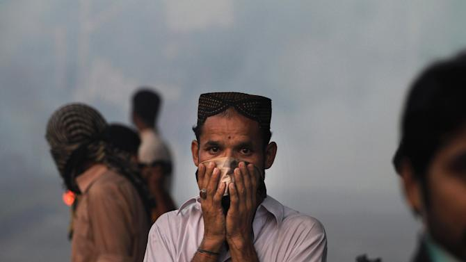 "A Pakistani protester reacts to tear gas during clashes that erupted as the demonstrators tried to approach the U.S. embassy in Islamabad, Pakistan, Friday, Sept. 21, 2012. Over a dozen people were killed as tens of thousands protested against an amateurish anti-Muslim film produced in the United States and vulgar caricatures of the Prophet Muhammad published in a French satirical weekly around the country after the government encouraged peaceful protests and declared a national holiday — ""Love for the Prophet Day."" (AP Photo/Anjum Naveed)"