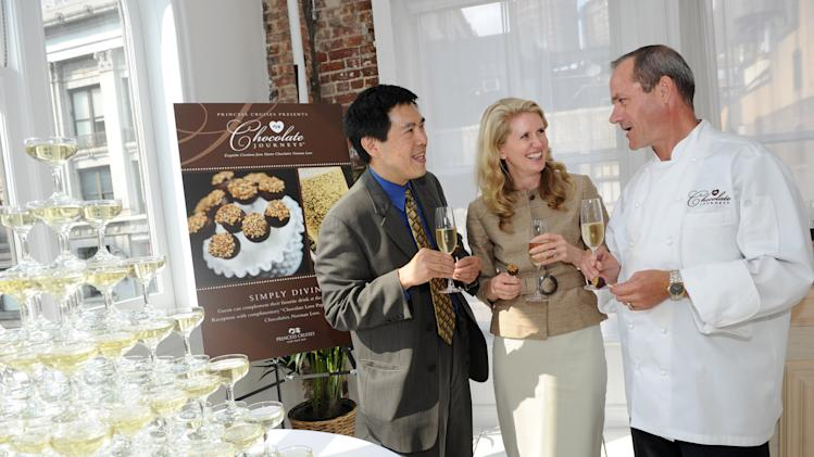 IMAGE DISTRIBUTED FOR PRINCESS CRUISES - Jan Swartz, center, President, Princess Cruises, Eric Le Rouzic, right, Corporate Pastry Chef, Princess Cruises, and Gordon Ho, SVP, Princess Cruises, enjoy a Chocolate Love Pop and Champagne after unveiling chocolate offerings to be featured exclusively on Chocolate Journeys, a premium chocolate experience on board Princess Cruises' fleet of ships, during an event in New York, Tuesday, July 29, 2014. (Photo Diane Bondareff/Invision for Princess Cruises/AP Images)