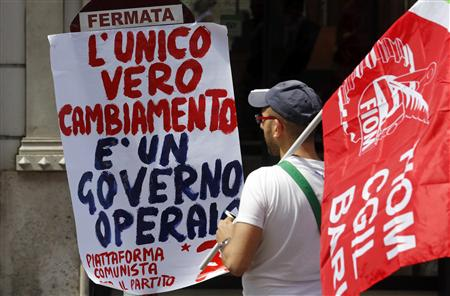 "A member of Italy's metalworkers union Fiom looks at a banner during a demonstration in Rome, May 18, 2013. The banner reads, ""The only way to change the government is to give it to the workers. real change, its a worker government."" REUTERS/Stefano Rellandini"