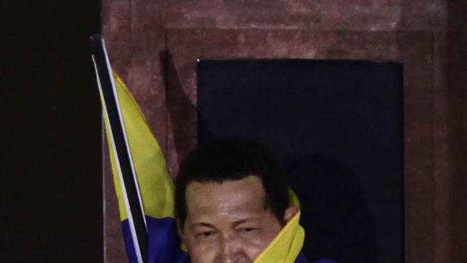 Venezuela's President Hugo Chavez wraps himself with a Venezuelan flag at a balcony of Miraflores presidential palace in Caracas, Venezuela, Thursday, July 28, 2011. Chavez sang on a balcony of the presidential palace as he celebrated his 57th birthday before a crowd of supporters, vowing to overcome cancer. (AP Photo/Ariana Cubillos)