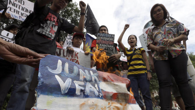 Protesters burn a mock American flag during a rally at the U.S. Embassy in Manila to protest the recent incident in the Philippines wherein a U.S. Navy minesweeper, USS Guardian, ran aground off Tubbataha Reef, a World Heritage Site in the Sulu Sea, 640 kilometers (400 miles) southwest of Manila, Philippines Saturday Jan. 19, 2013. The protesters are demanding the abrogation of the Visiting Forces Agreement which allows U.S. troops' presence in the country.  (AP Photo/Bullit Marquez)