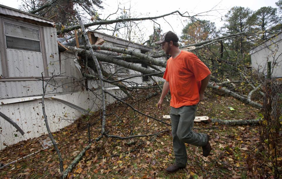 Chad Scott inspects damage to his cousins home in Auburn, Ala., Wednesday, Nov. 16, 2011.  A path of storms swept across the state leaving behind fallen trees and some heavy wind damage.  (AP Photo/Dave Martin)
