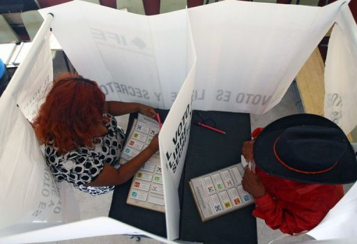 <p>Mexicans vote at a polling station in Ciudad Juarez, Mexico. Mexico's cartels cast an ugly shadow over Sunday's elections, the heavy police and military presence doing little to quell the fears of anxious voters in areas worst affected by the country's rampant drug violence.</p>