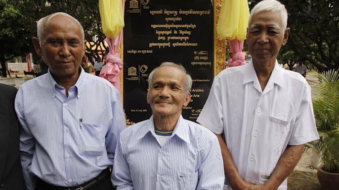 In this photo taken, Aug. 9, 2010, Cambodian survivors, Vann Nath, 66, from right,  Bou Meng, 70, Chum Mey, 81, pose for a photograph at Tuol Sleng genocide museum, formerly Khmer Rouge's notorious S-21 prison in Phnom Penh, Cambodia. Nath lapsed into a coma in late August, 2011, after developing breathing difficulties, and his daughter Vann Chan Simen says he passed away on Monday, Sept. 5. (AP Photo/Heng Sinith)