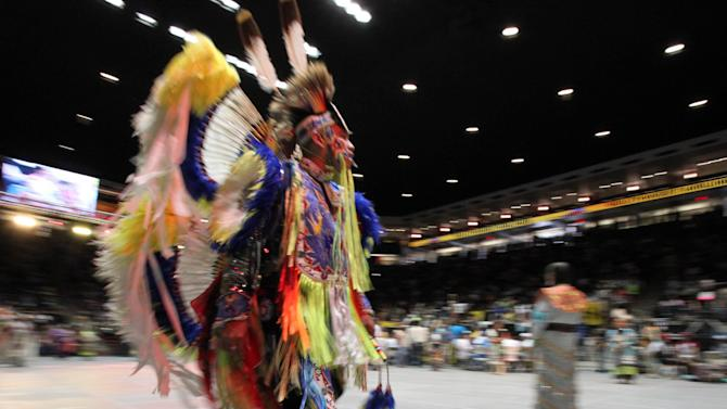 A native dancer walks by during the 29th annual Gathering of Nations in Albuquerque, N.M., on Friday April 27, 2012. The event draws more than 3,000 dancers and singers and tens of thousands of spectators for three days of competitions and the crowning of Miss Indian World. (AP Photo/Susan Montoya Bryan)