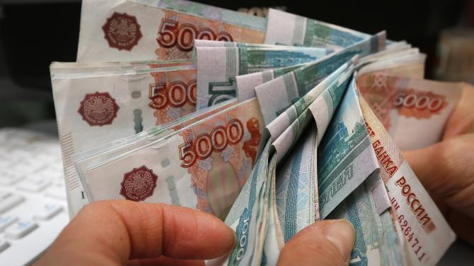 An employee counts Russian rouble banknotes at a small private shop in Krasnoyarsk