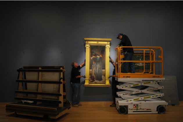 Workers install one of three paintings on loan from New York's Metropolitan Museum of Art, at the Museum of Fine Arts, Boston in Boston