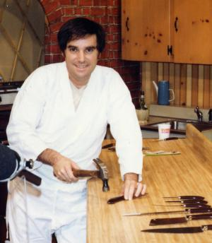 """In this 1978 photo made available by PriMedia shows Barry Becher at a studio using a hammer on a Ginsu knife. Becher, a marketing mastermind and infomercial pioneer best know for bringing Ginsu knives to the American public, died of complications from surgery. He was 71. Becher was buried in Tamarac, Fla., on Monday, June 25, 2012. His family is considering etching in his tombstone one of the carchphrases he help popularize: """"But wait, there's more."""" (AP Photo/PriMedia)"""