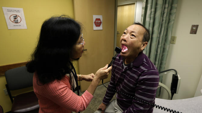 Chan Lai Ly, right, has his mouth examined as part of a regular check-up related to his diabetes, by Honghue Duong, left, a physician's assistant, Friday, March 1, 2013 at International Community Health Services in Seattle. The clinic, which serves patients who speak more than 50 different languages, illustrates a challenge Washington state will face as it launches its new health insurance exchange as part of the federal Affordable Care Act. (AP Photo/Ted S. Warren)