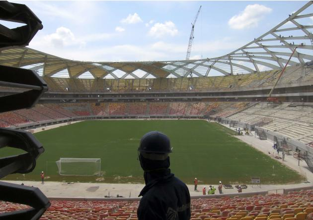 A workman looks out at the pitch inside the Arena Amazonia stadium as work continues in preparation for the 2014 FIFA World Cup soccer championship in Manaus