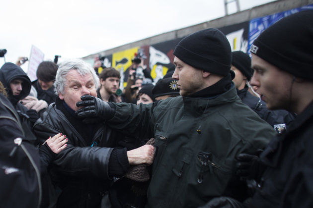German police struggles with a protestor as they protect a part of the former Berlin Wall in Berlin, Germany, Friday, March 1, 2013. Berliners are protesting as a construction company removes a sectio