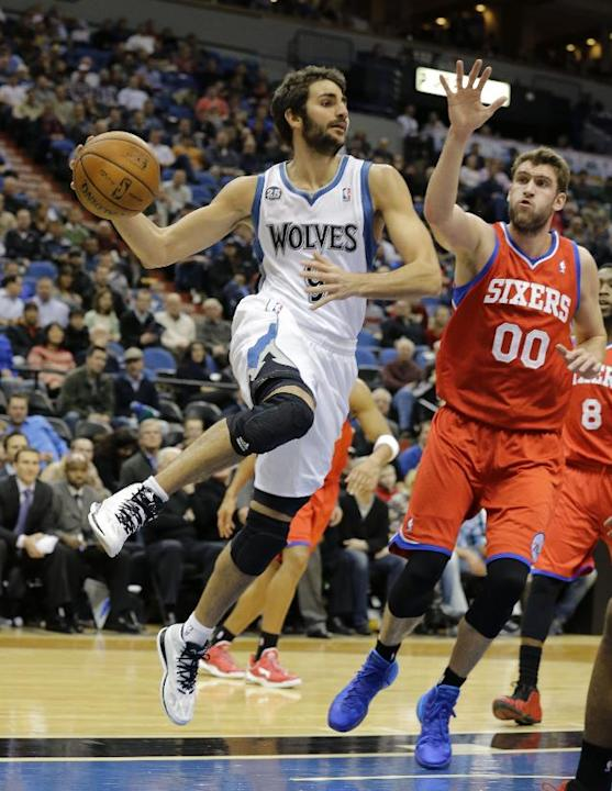 Minnesota Timberwolves guard Ricky Rubio, left, of Spain, turns to pass to a teammate around Philadelphia 76ers center Spencer Hawes (00) during the third quarter of an NBA basketball game in Minneapo