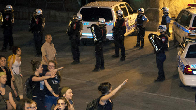 Protesters gesture at Montreal riot police as they guard the back entrance at the headquarters of the Quebec Provincial police during the nightly protest march against tuition fee hikes and new legislation controlling protests in Montreal on Monday, May 21, 2012. (AP Photo/The Canadian Press, Peter McCabe)