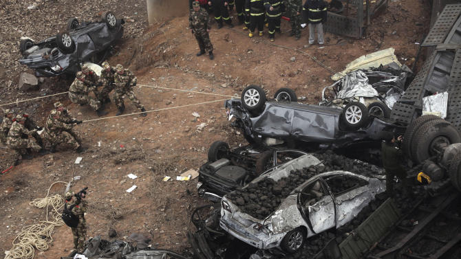 Chinese paramilitary policemen pull at car wreckage at the accident site where an expressway bridge partially collapsed due to a truck explosion in Mianchi County, Sanmenxia, central China's Henan Province, Thursday, Feb. 1, 2013. A truckload of fireworks intended for Lunar New Year celebrations went off Friday in a massive, deadly explosion that destroyed part of an elevated highway in central China, sending vehicles plummeting 30 meters (about 100 feet) to the ground. (AP Photo) CHINA OUT