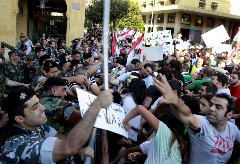 Lebanese riot police scuffle with protesters near Parliament during a demonstration in Beirut, Lebanon, Thursday, June 20, 2013. Lebanon's parliament on May 29 extended its term by a year and a half, skipping scheduled elections because of the country's deteriorating security linked to the civil war next door in Syria. (AP Photo/Bilal Hussein)