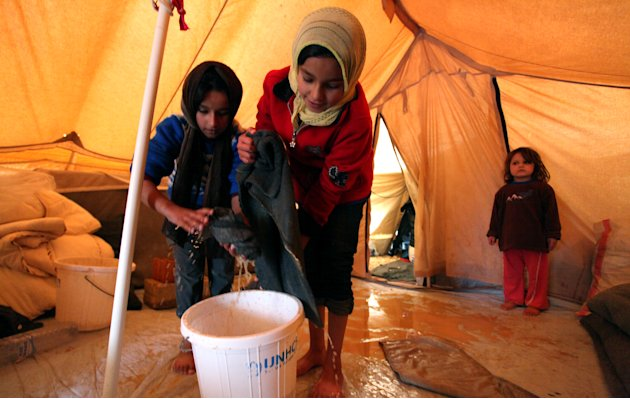 Syrian refugee girls remove water and mud from their tent after a flood at Zaatari Syrian refugee camp, near the Syrian border in Mafraq, Jordan, Tuesday, Jan. 8, 2013. Syrian refugees in a Jordanian 