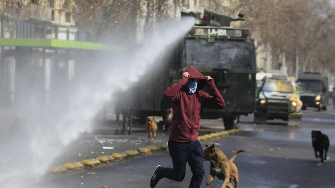 A masked protester runs away from a water cannon, during a student protest in Santiago, Chile, Thursday, Aug. 21, 2014. Tens of thousands of students protested in the third massive march of the year in Chile. The students are unhappy with the pace of education reform that President Michelle Bachelet has been moving forward. (AP Photo / Luis Hidalgo)