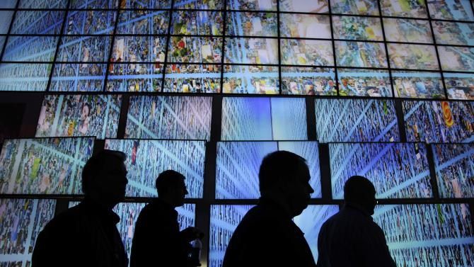 FILE - In this Thursday, Jan. 6, 2011, file photo, exhibitors and buyers at the Consumer Electronics Show walk by a display of LG HDTV screens, in Las Vegas. An Associated Press investigation released in January 2013 found that millions of mid-skill, mid-pay jobs have disappeared over the past five years and have been replaced with technology. That experience has left some economists to worry that smarter machines and niftier software will continue to replace more and more midpay jobs, making businesses more productive and swelling their profits. (AP Photo/Julie Jacobson, File)