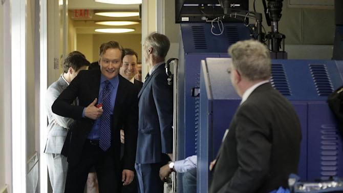 Late-night television host and comedian Conan O'Brien gives a 'thumbs-up' as he tours the Brady Press Briefing room of the White House in Washington, Friday, April, 26, 2013. O'Brien visited the White House ahead of his schedule hosting of the annual White House Correspondents Dinner on Saturday. (AP Photo/Pablo Martinez Monsivais)