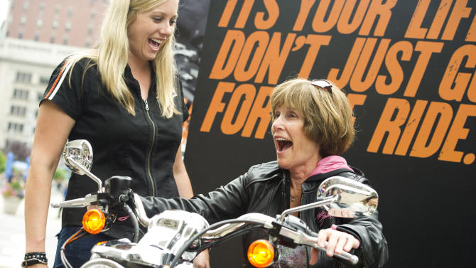 This June 13, 2012 photo shows Harley-Davidson representative Dana Wilke, left, smiling as Nancy Dilley, 68, of Overland Park, Kan., learns the basics while test riding a motorcycle in New York. Harley-Davidson, based in Milwaukee, is the market leader in sales to women. The company travels around the country offering training and safety tips for women. (AP Photo/Charles Sykes)