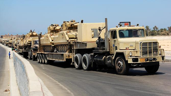 FILE - In this Aug. 9, 2012 file photo,  army trucks carry Egyptian military tanks in El Arish, Egypt's northern Sinai Peninsula. Israeli officials said Tuesday, Aug. 21, 2012 they have voiced objections to what they say are improper Egyptian tank deployments in a volatile desert area near the Israeli border. Israel says the deployment, part of an Egyptian crackdown on Islamic militants in the lawless Sinai desert, violate the historic 1979 peace agreement between the two nations. (AP Photo, File)