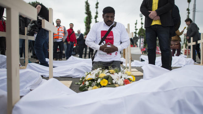 "Activists have set up wooden crosses during a protest called ""Red Card for FIFA. No World Cup in Qatar without Workers rights!"" that was organized by the Swiss trade union UNIA in front of the Hallenstadion in Zurich, Switzerland, Friday, May 29, 2015. The demonstrators ask FIFA to improve conditions for workers at the stadium's construction sites. (Ennio Leanza/Keystone via AP)"