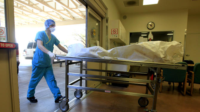 In this Aug. 10, 2012 photo, a morgue staff member brings in the body of a suspected illegal immigrant found in the Arizona desert, at the Pima County morgue in Tucson, Ariz.  The death of migrants crossing the Southwest border has long been a tragic consequence of illegal immigration and, many say, the massive increase in U.S. border enforcement. For some, the tragedies are a powerful motivator in pushing Congress to act this year on a larger immigration reform package.  (AP Photo/Ross D. Franklin)