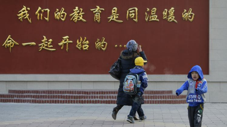 Liu Fei, 41-year-old warehouse worker, takes her son Xiaojie to school in Fangshan, district of Beijing