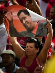 A supporter of Venezuelan President Hugo Chavez holds a poster depicting him during an electoral rally in Caracas on June 1. In a crowded square of the biggest shantytown in Caracas, Chavez&#39;s reelection campaign wheels are spinning. But a bit like a movie missing its star, the president is not on the trail