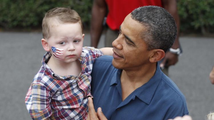 President Barack Obama picks up a child as he greets military families at an Independence Day celebration on the South Lawn of the White House in Washington, Monday, July 4, 2011. (AP Photo/Charles Dharapak)