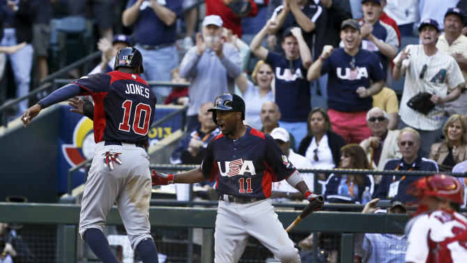 United States' Adam Jones (10) celebrates his run scored against Canada with teammate Jimmy Rollins (11) in the eighth inning during a World Baseball Classic baseball game on Sunday, March 10, 2013, in Phoenix.  The United States defeated Canada 9-4. (AP Photo/Ross D. Franklin)