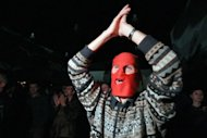 A Russian opposition supporter, wearing a red balaclava, shouts and applauses during a concert in support of Pussy Riot on September 9. The band plans a new protest in Russia despite the jailing of three of its members for a performance against Vladimir Putin in an Orthodox cathedral, band members said