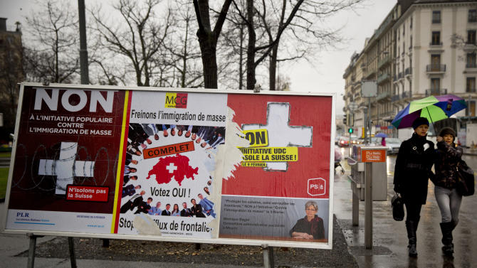 """Women pass by election placards , poster in center is for a stop of immigration, and posters at left and at right are for a yes to immigration, in Geneva, Switzerland, Monday, Feb. 10, 2014. The placard in the center reads ' stop the influence from the border'. The choice by Swiss voters to reimpose curbs on immigration is sending shock waves throughout the European Union, with EU leaders on Monday warning the Swiss had violated the """"sacred principle"""" of Europeans' freedom of movement and politicians anxiously trying to gauge the vote's impact on burgeoning anti-foreigner movements in other countries. (AP Photo/Anja Niedringhaus)"""