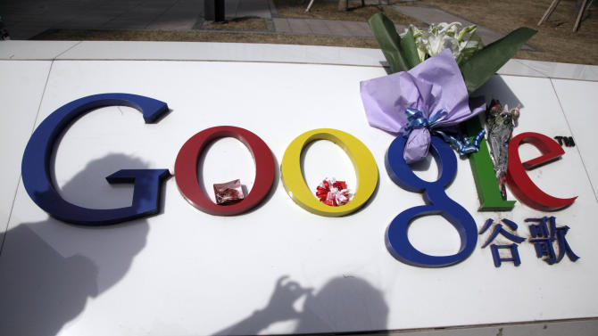 FILE - In this March 23, 2010 file photo, flowers are placed on the Google logo outside Google China headquarters in Beijing, China. Google has fired a new salvo in a censorship battle with Beijing by adding a feature that suggests alternatives for search terms that might result in blocked results. (AP Photo/Ng Han Guan, File)