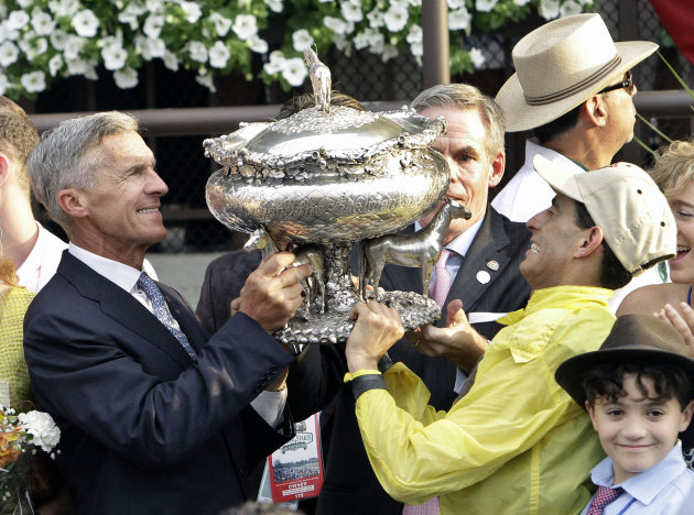 Trainer Michael Matz, left, tries to hoist the Belmont Stakes trophy with jockey John Velazquez, right, after Union Rags captured the Belmont Stakes horse race at Belmont Park n Elmont, N.Y., Saturday, June 9, 2012. (AP Photo/Garry Jones)