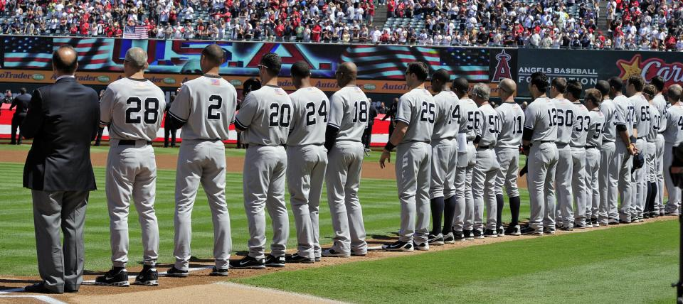 Members of the New York Yankees stand during a ceremony to commemorate the Sept. 11, 2001 terrorist attacks prior to the Yankees baseball game against the Los Angeles Angels, Sunday, Sept. 11, 2011, in Anaheim, Calif.  (AP Photo/Mark J. Terrill)