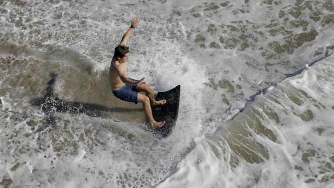 A boogie boarder rides a wave in the surf Friday, Feb. 12, 2016 in Seal Beach, Calif. Ten days with record heat and no rain have Californians worrying about the drought again. (AP Photo/Chris Carlson)