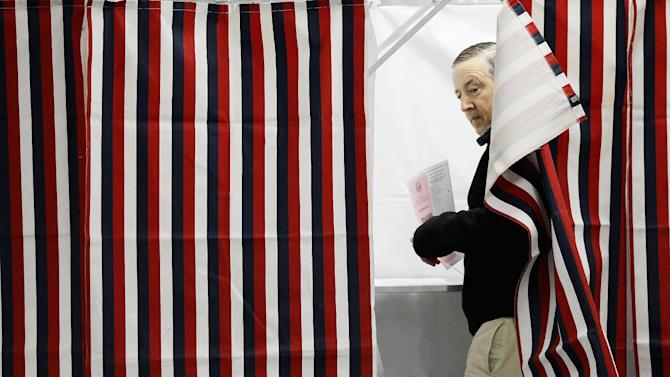 Mike Fahey steps out of a voting booth after marking his ballot for the New Hampshire primary at a polling site, Tuesday, Feb. 9, 2016, in Nashua, N.H. (AP Photo/David Goldman)