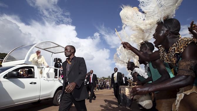 Performers wearing traditional tribal clothings greet Pope Francis as he arrives at Kololo Air strip for a meeting with youths in Kampala