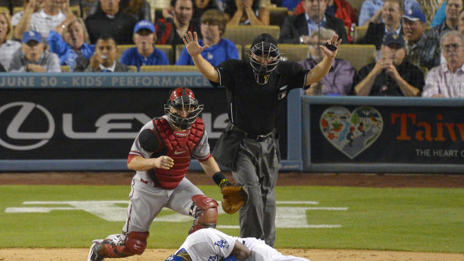 Los Angeles Dodgers' Yasiel Puig, below, is seen to by Arizona Diamondbacks catcher Miguel Montero after being grazed by a pitch as home plate umpire Clint Fagan signals during the sixth inning of their baseball game, Tuesday, June 11, 2013, in Los Angeles.  (AP Photo/Mark J. Terrill)