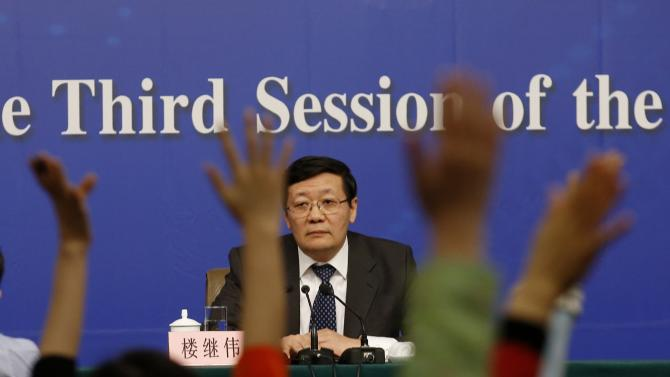Journalists raise their hands to ask questions to China's Finance Minister Lou Jiwei at a news conference  in Beijing