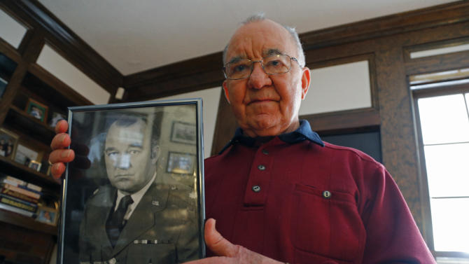 In this Dec. 13, 2012 photo, Howard Rowell shows a photo of himself when he retired from the Air Force Reserve at his home in Columbia, S.C. Rowell is concerned about the possibility of cuts that could chip away at military health insurance, pensions and other services long considered untouchable. If Congress and President Barack Obama don't agree on spending cuts by Jan. 1, a package of across-the-board cuts would take effect that would hit the military heavily. (AP Photo/Chuck Burton)