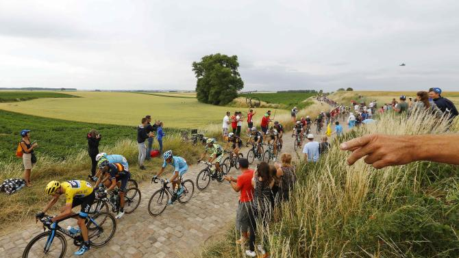 Team Sky rider Froome of Britain cycles on a cobble-stoned section during the 4th stage of the 102nd Tour de France cycling race from Seraing to Cambrai