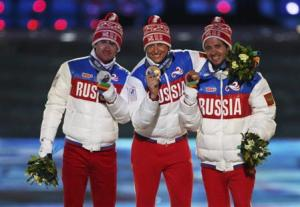Russia's gold medallist Legkov poses with compatriots silver medallist Vylegzhanin and bronze medallist Chernousov after being presented with medals for men's cross-country 50km mass start free event during closing ceremony of Sochi Winter Olympics