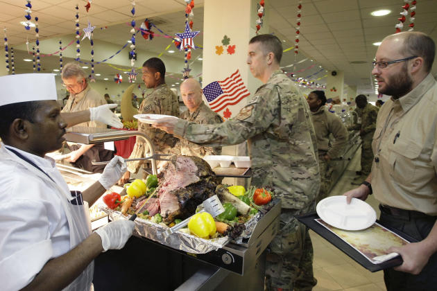 A dining facility worker, left, serves meat to soldiers and civilians for their Thanksgiving meal at the U.S.-led coalition base in Kabul, Afghanistan, Thursday, Nov. 22, 2012. The dining hall at the