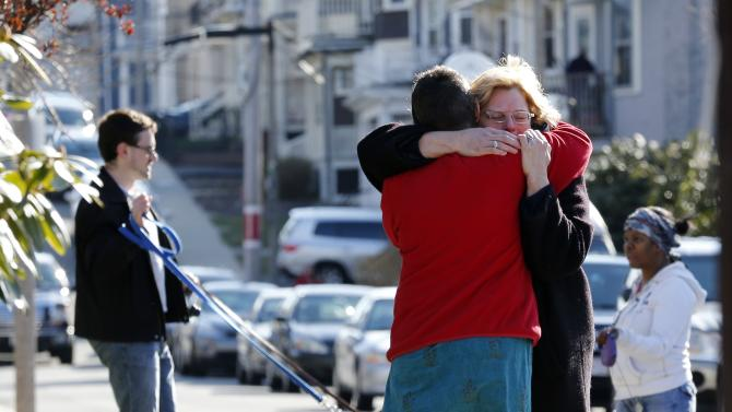 Neighbors hug outside the home of the Richard family in the Dorchester neighborhood of Boston, Tuesday, April 16, 2013.  Martin Richard, 8, was killed in Monday's bombing at the finish line of the Boston Marathon. (AP Photo/Michael Dwyer)