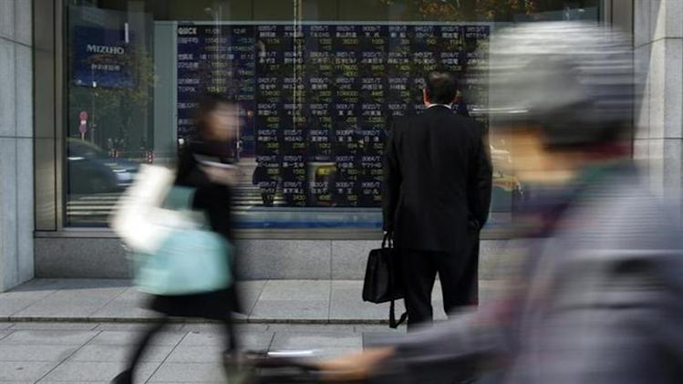 A pedestrian looks at a stock quotation board outside a brokerage in Tokyo November 26, 2013.