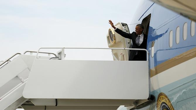 Obama waves as he boards Air Force One for travel to Alaska from Joint Base Andrews