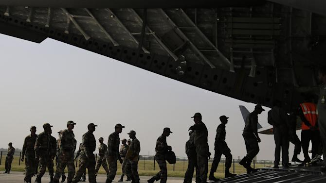 Indian soldiers on rescue mission to Nepal, board an Indian Air Force aircraft near New Delhi, India, Sunday, April 26, 2015. A strong magnitude-7.9 earthquake shook Nepal's capital and the densely populated Kathmandu Valley before noon Saturday, causing extensive damage with toppled walls and collapsed buildings, officials said.(AP Photo/Altaf Qadri)